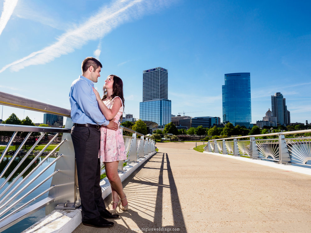 A couple in love embraces on a bridge overlooking the city of Milwaukee.