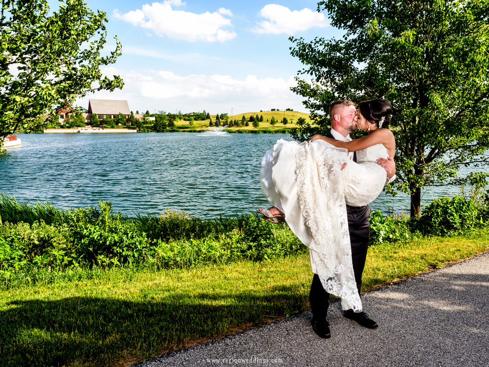 The groom lifts his bride off of her feet at their summer wedding.