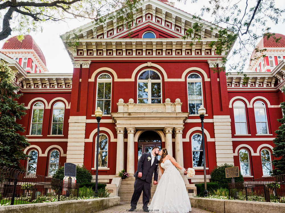 Bride and groom kiss in front of the Old Courthouse in Crown Point, Indiana