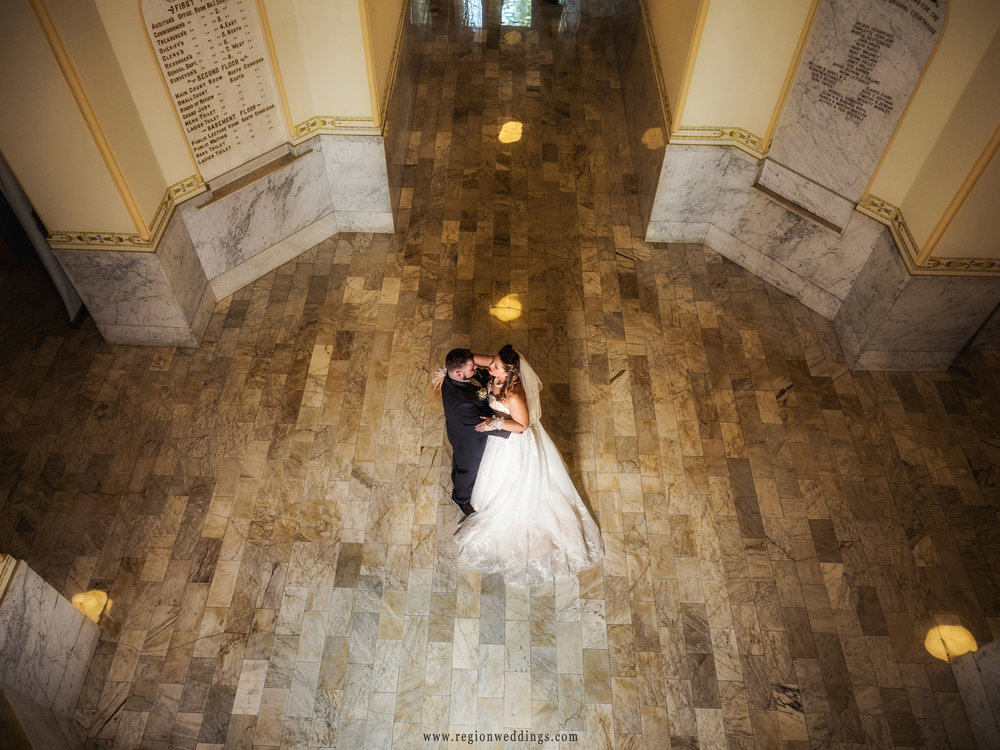Bride and groom slow dance on the vintage lobby floor of the Old Crown Point Courthouse.