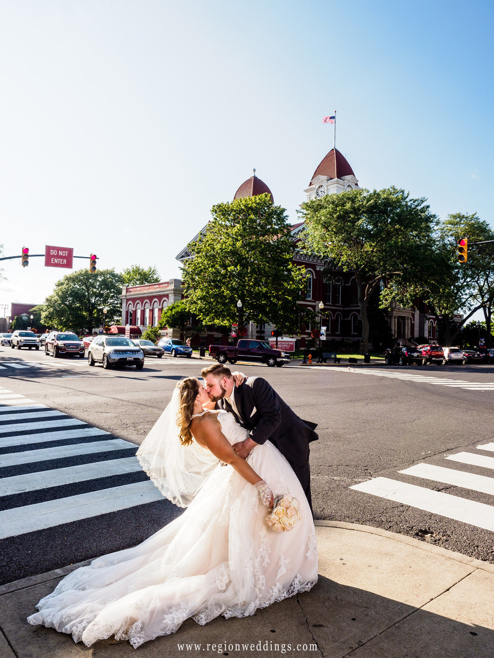 The groom dips his bride in downtown Crown Point, Indiana.