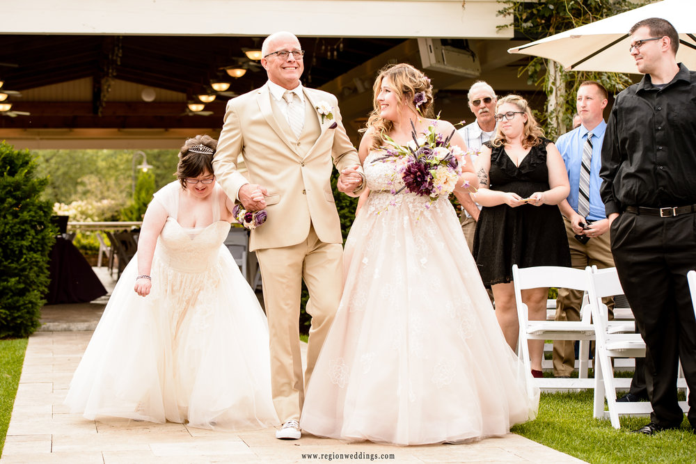 Dad walks his two daughters down the aisle.