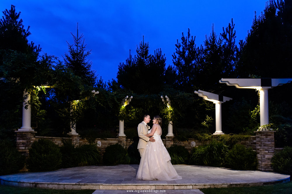 The bride and groom dance underneath the stars at their summer wedding.