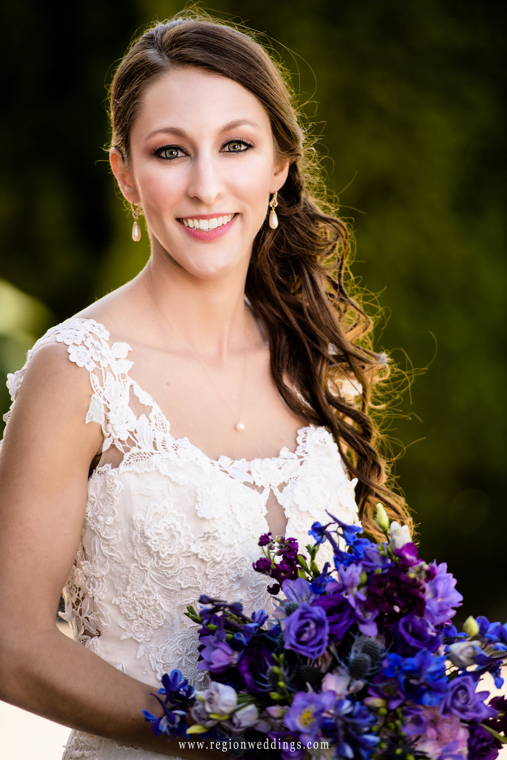 Beautiful bride with a purple and blue bouquet of flowers.