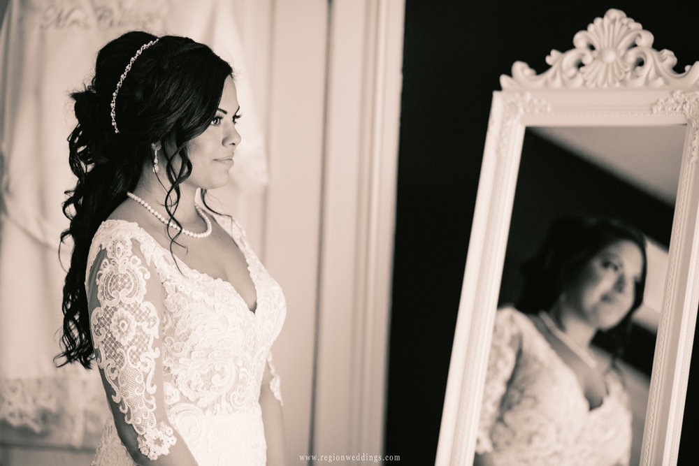 The bride reflected in the mirror illuminated by window light.
