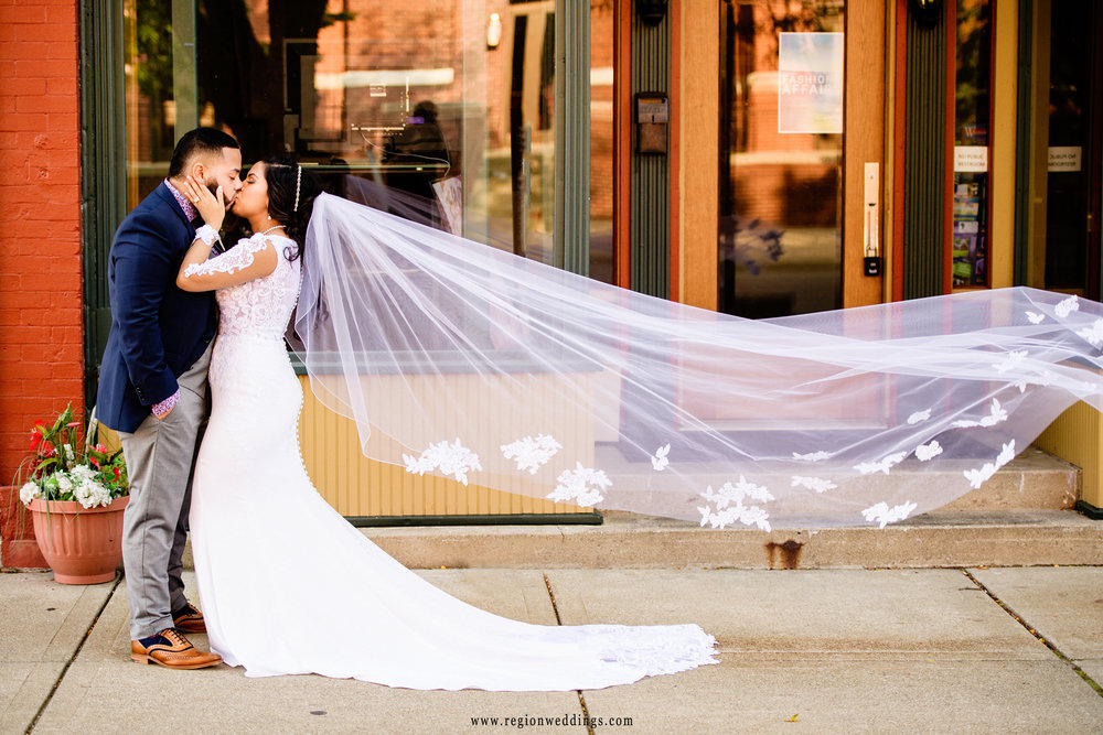 The bride's veil flies into the air as she kisses the groom on the city street.