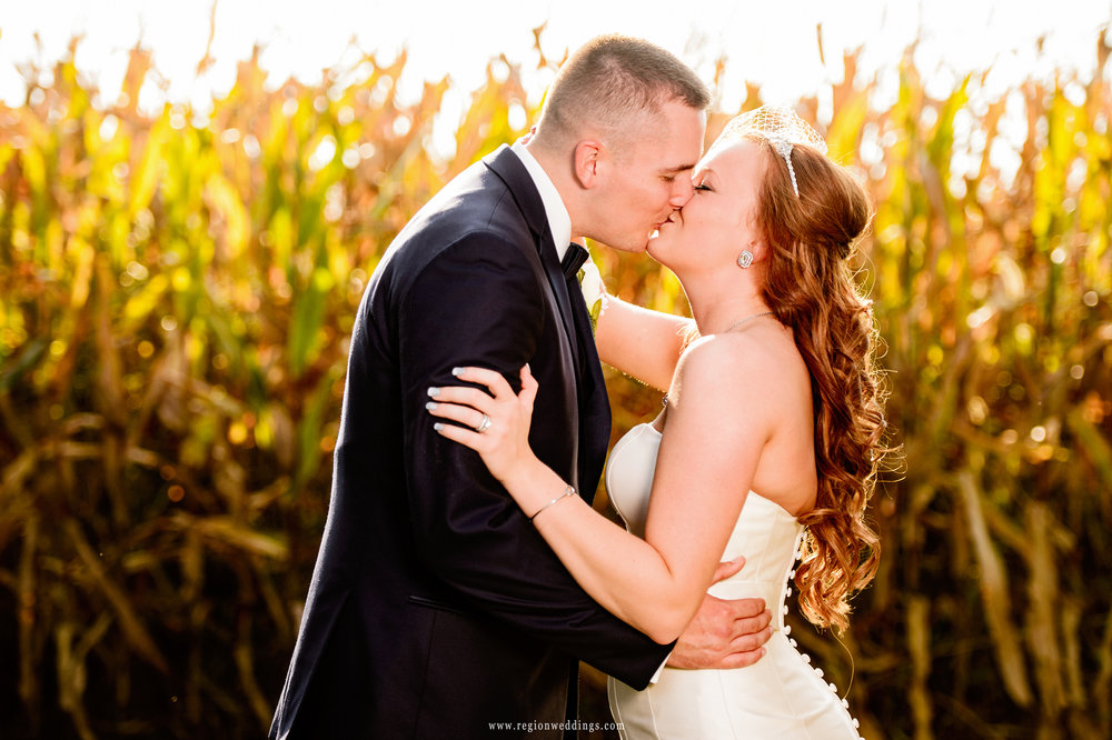 A kiss for the bride and groom in the Indiana cornfields.