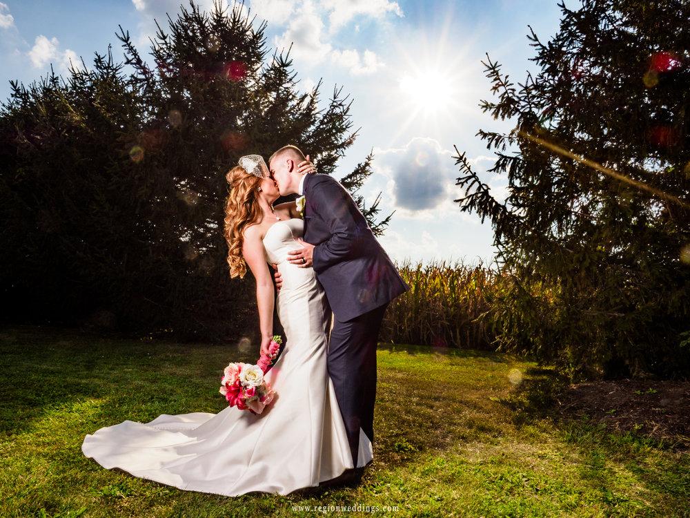 The bride and groom share a kiss as the bright sun illuminates them on an Indiana farm.