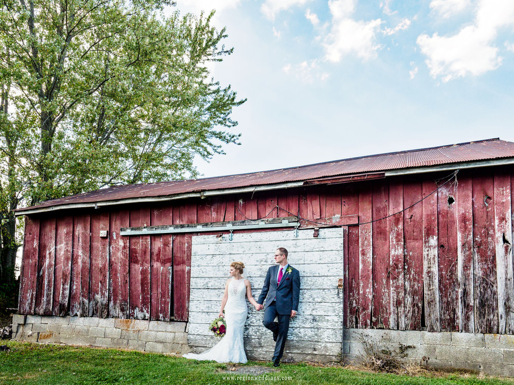 The bride and groom in front of an old weathered barn.