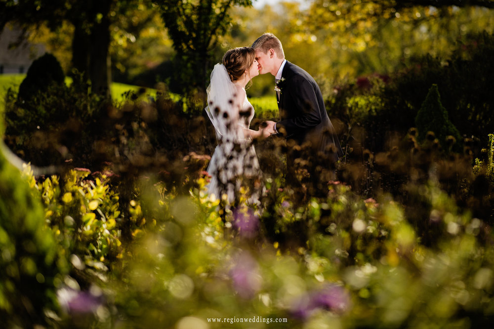 Bride and groom share a romantic kiss in the Sand Creek garden in Chesterton, Indiana.