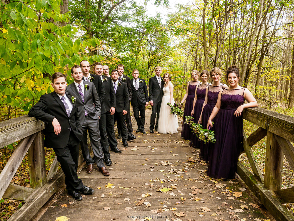 Wedding party photo on a leaf covered bridge.