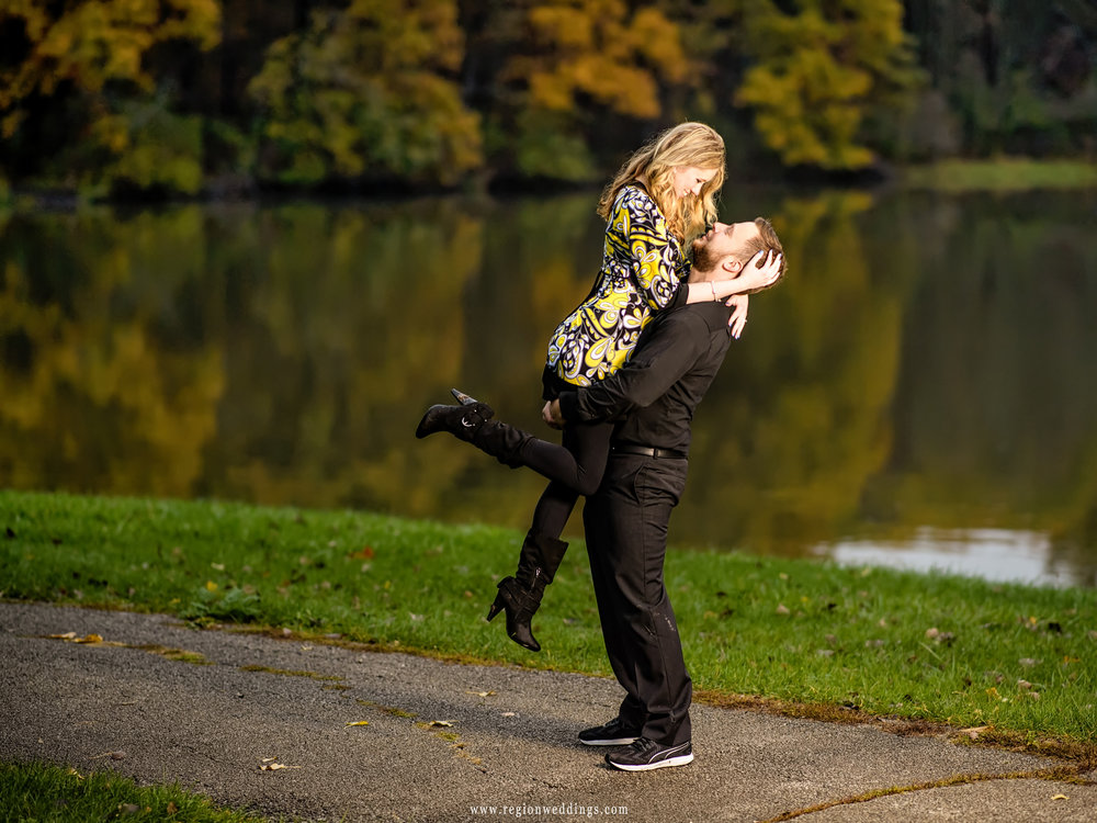 Two lovers play along the lakefront during their Fall engagement session.