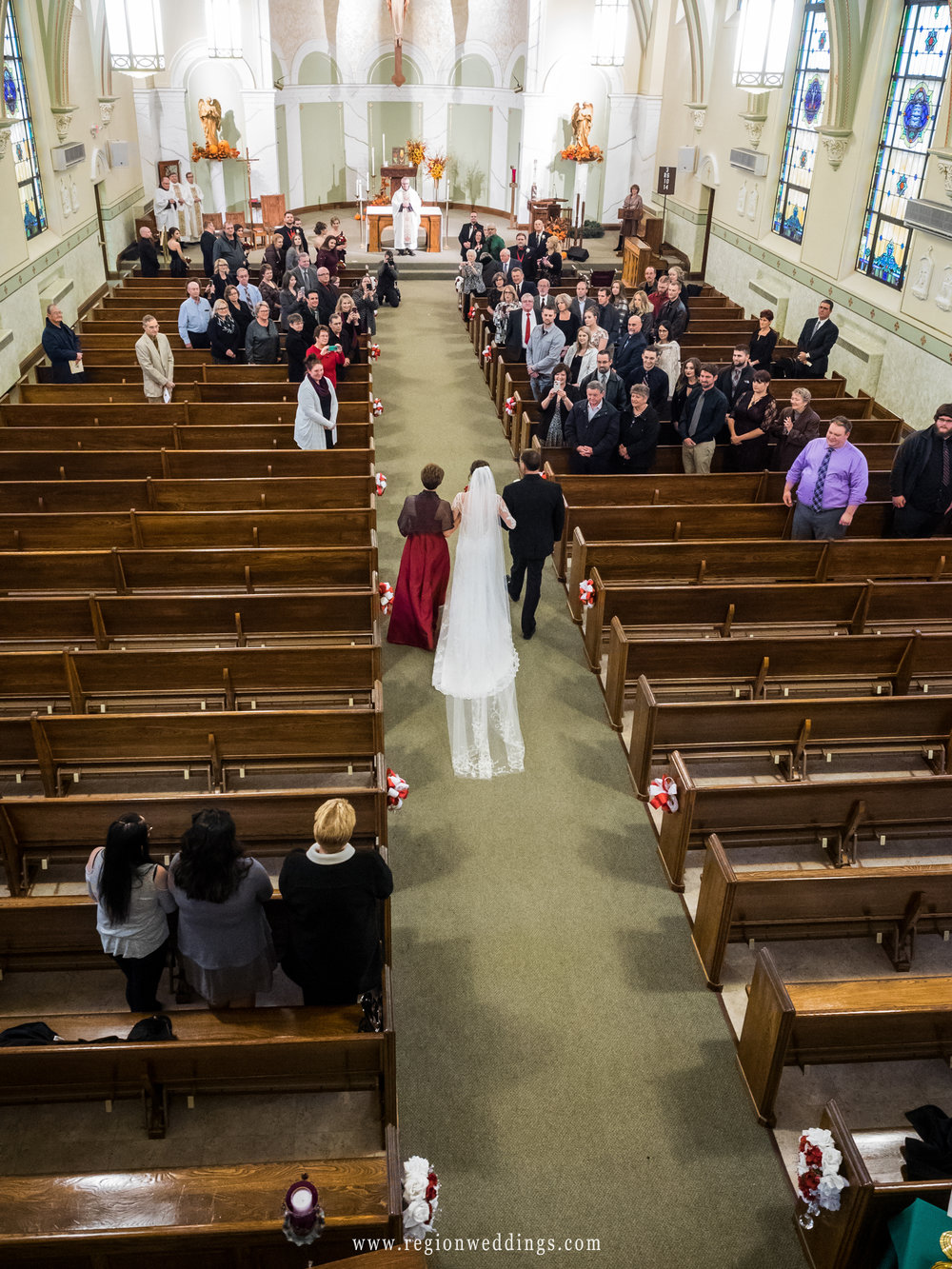 The bride walks down the aisle at Holy Name Catholic Church.