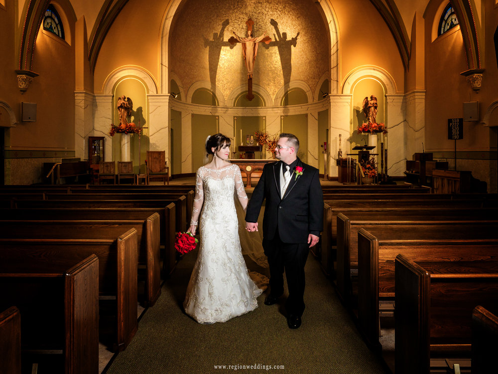 Bride and groom walk down the aisle at Holy Name Catholic Church in Cedar Lake, Indiana.