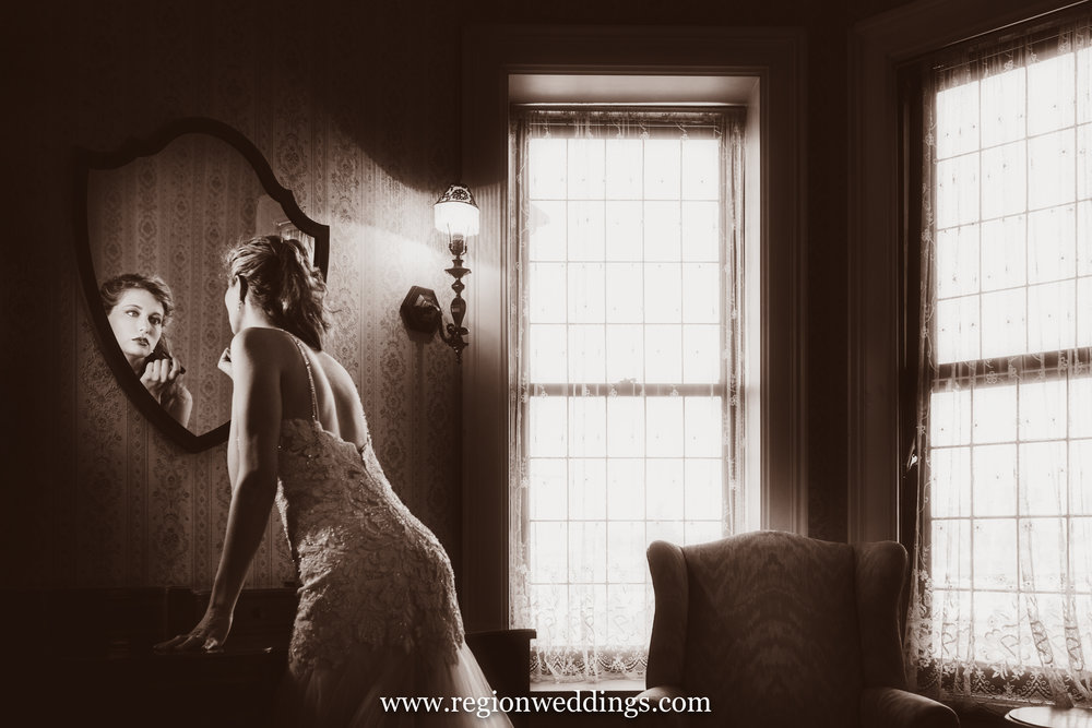 Bride applies lipstick at Barker Mansion in Michigan City, Indiana.