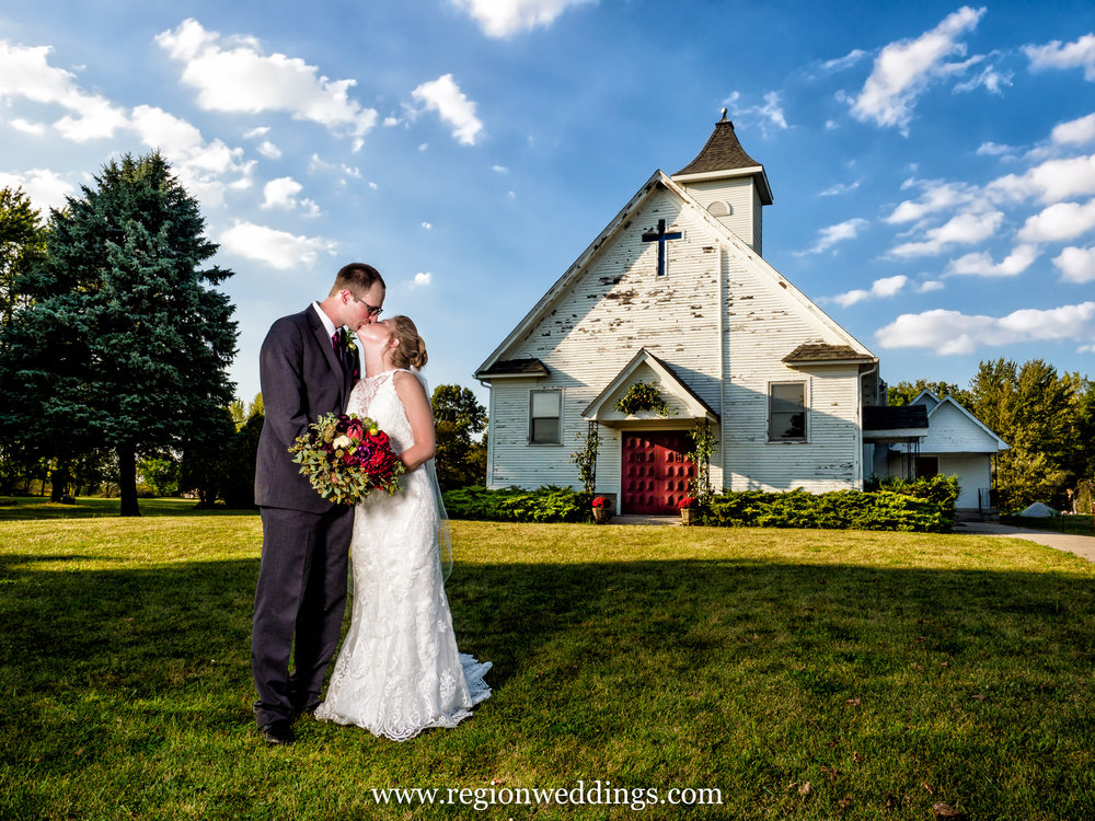 Bride and groom kiss in front an old chapel in Hebron, Indiana.
