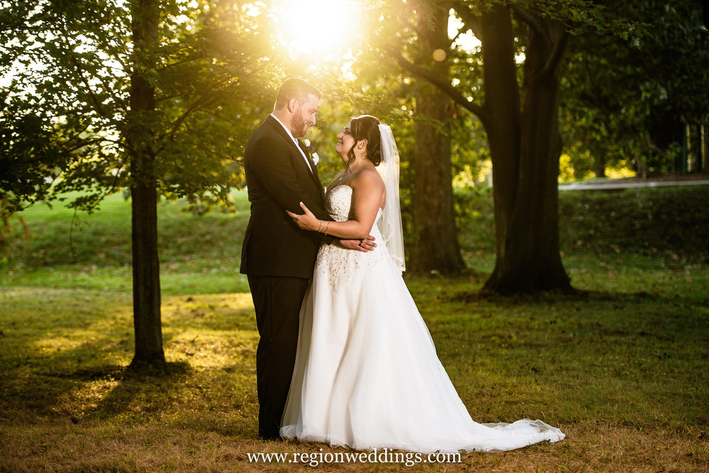 The sun sets as the bride and groom gaze at each other beneath the tall trees in the forest.