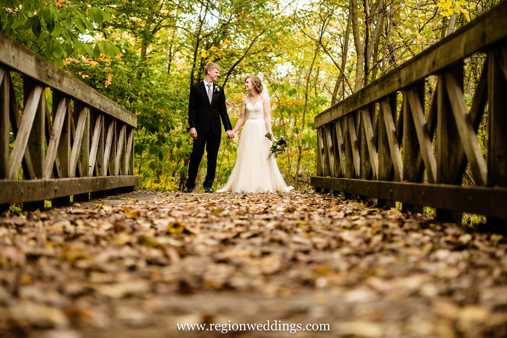 Bride and groom on a leaf filled bridge near Coffee Creek in Chesterton, Indiana.