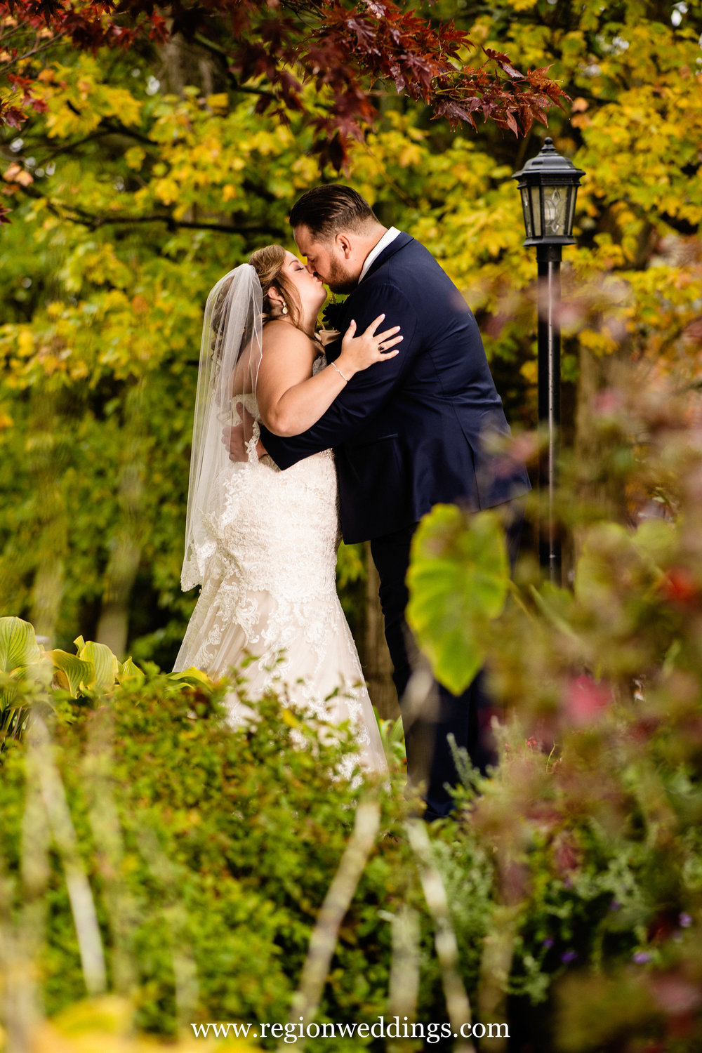 The bride and groom share a kiss surrounded by Fall color at The Inn At Aberdeen.