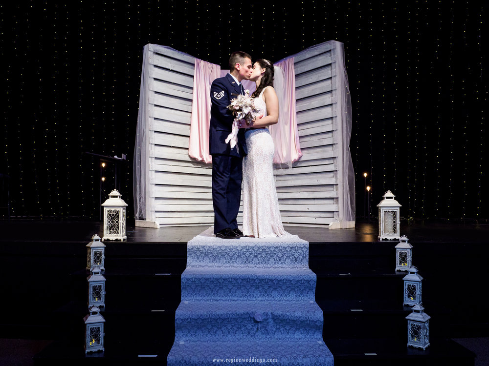 Bride and groom kiss on the stage at Bethel Church.