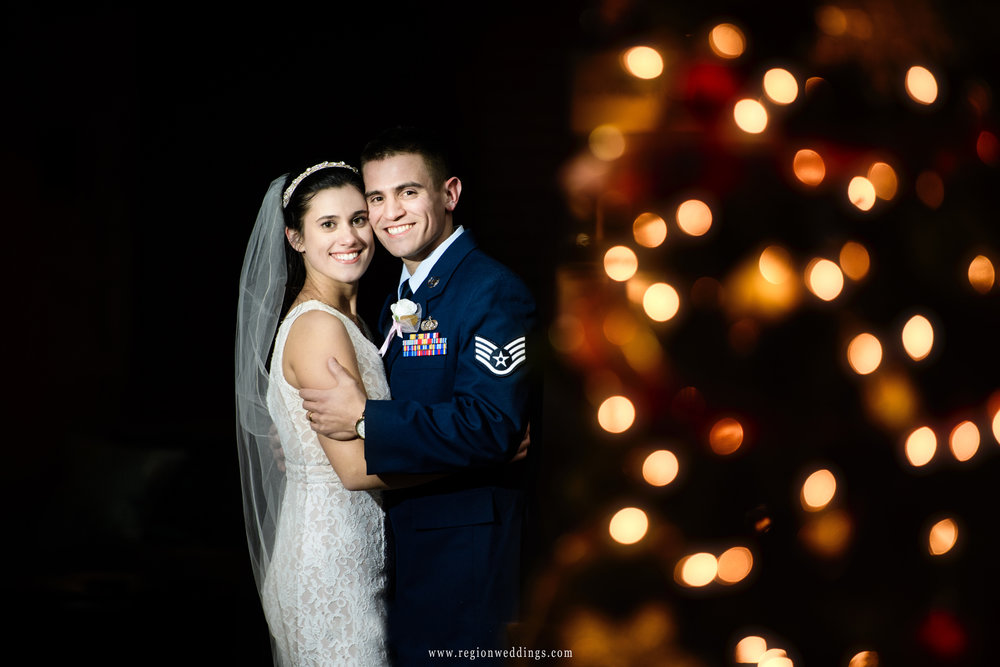 The bride and groom next to Christmas tree lights at Bethel Church.