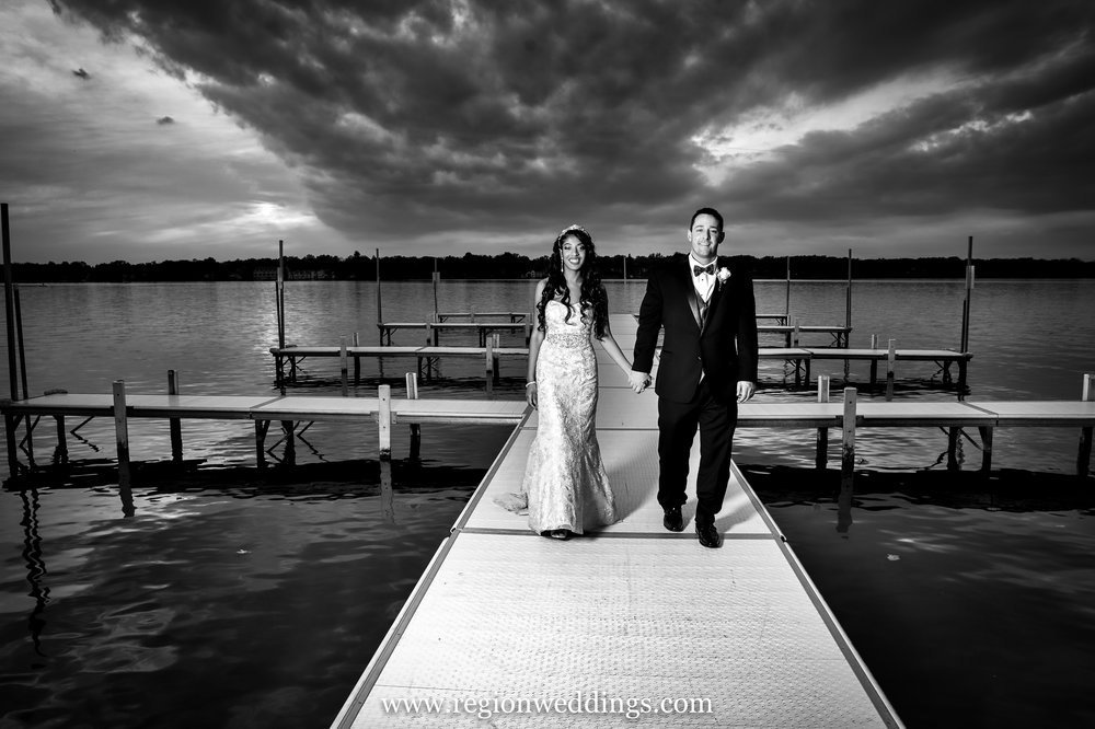 A romantic walk on a pier for the bride and groom in a black and white wedding picture.
