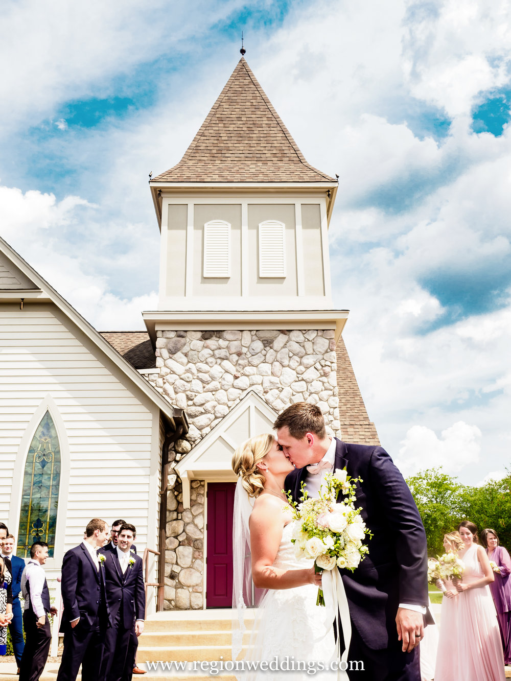 Church bells ring as the bride and groom exit Aberdeen Chapel in Valparaiso, Indiana.