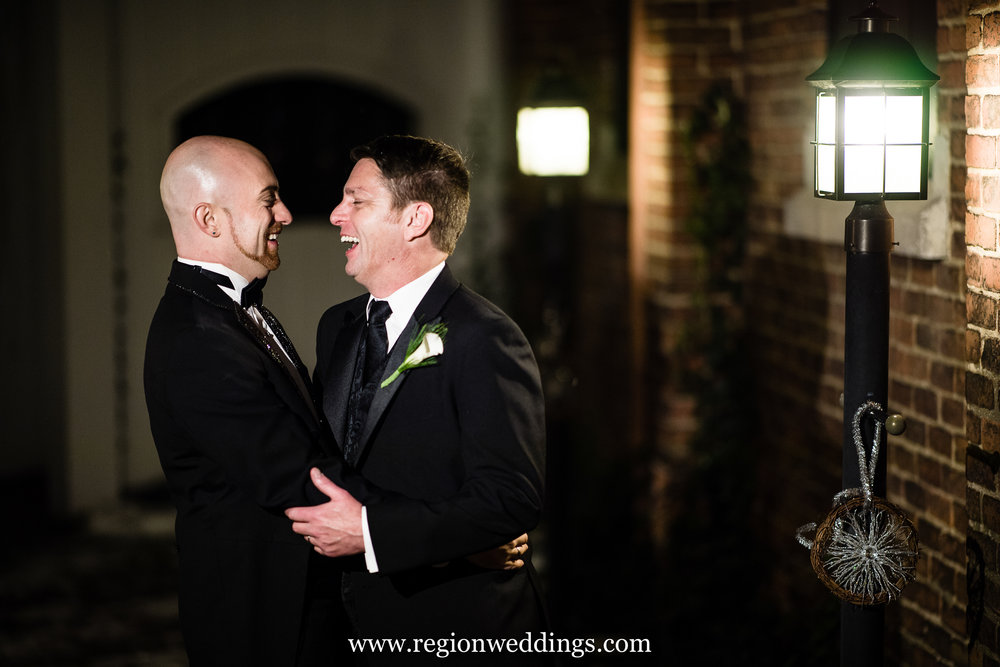 Two grooms share a moment of laughter in the courtyard of Uptown Center.