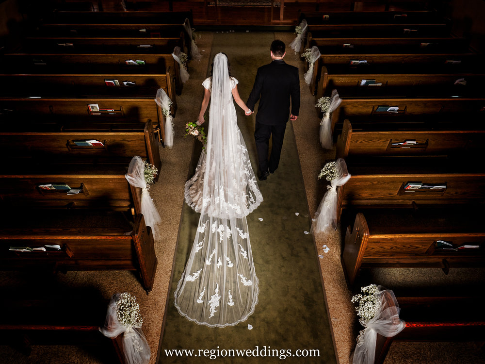 Newlyweds walk down the aisle at Immaculate Heart Of Mary Church