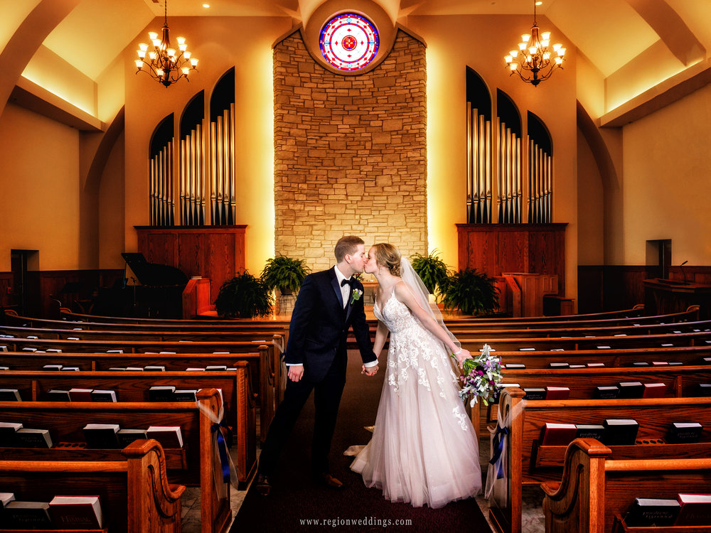 Bride and groom share a kiss during portraits inside church.