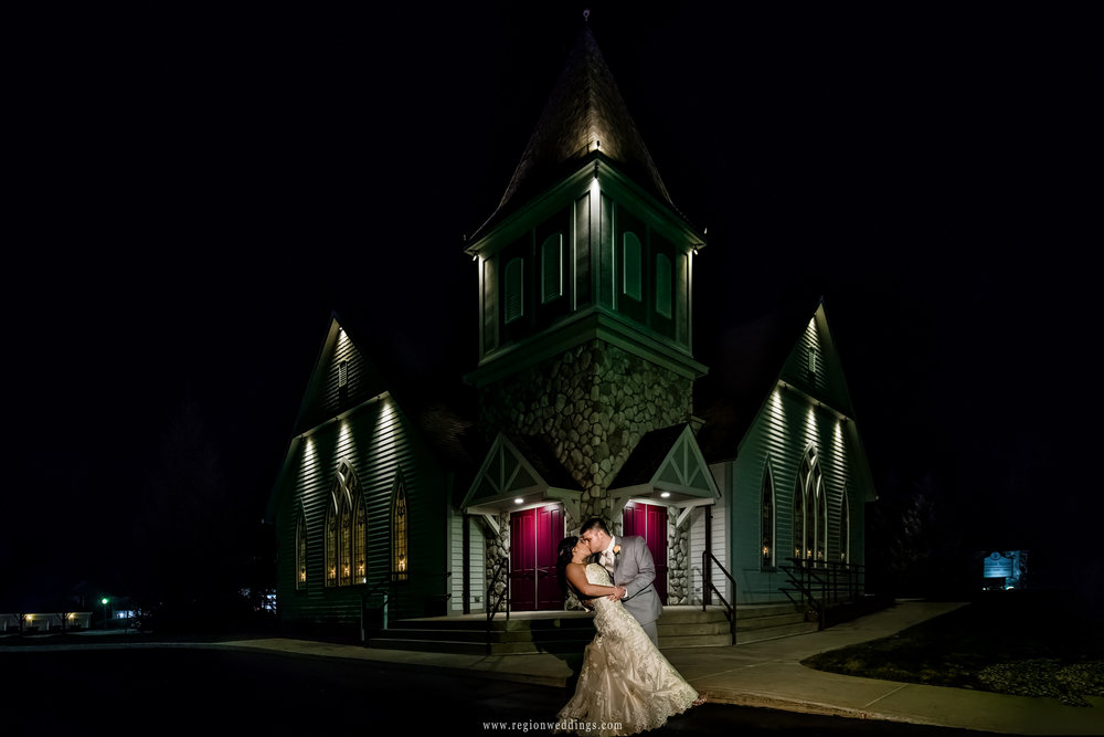 The groom dips his bride at night in front of the Aberdeen Chapel.
