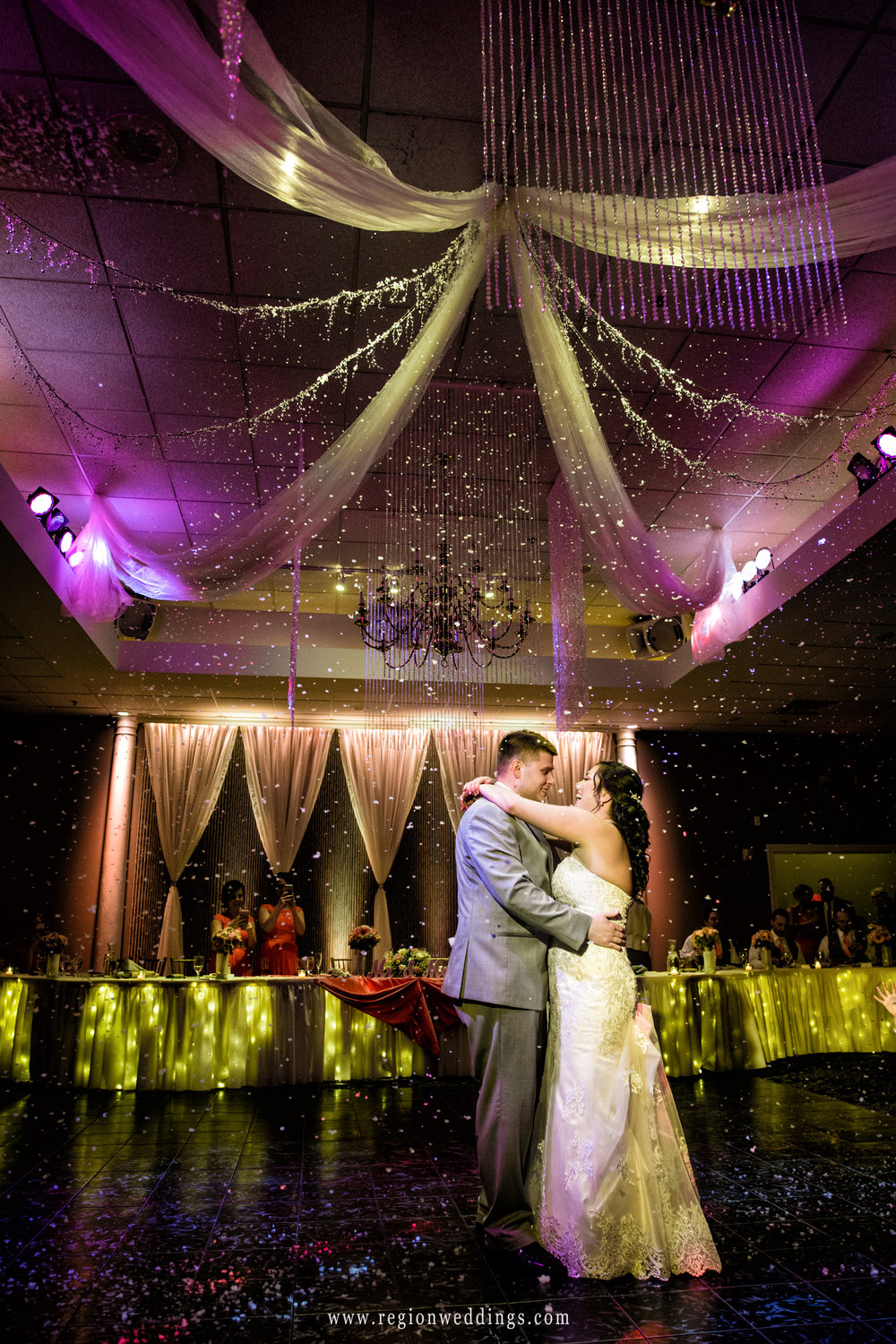 Light confetti falls upon the bride and groom during their first dance.