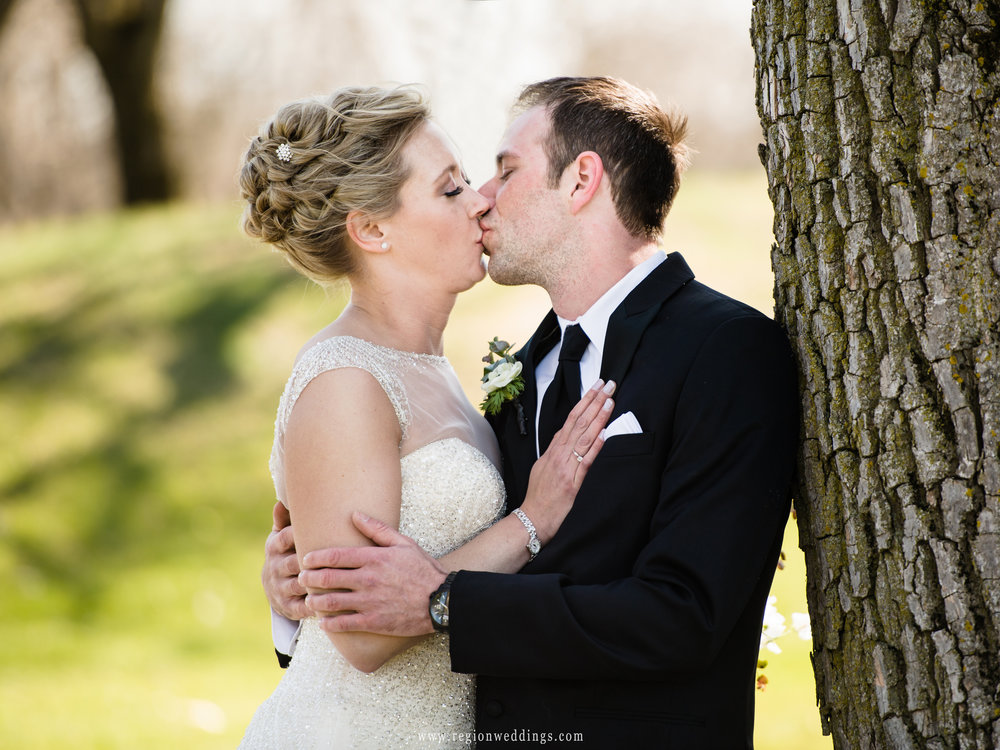 The groom kisses his bride in the shade on the golf course.