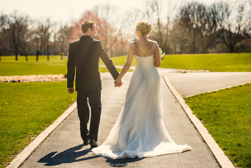The bride and groom walk into the sun on the golf course at Briar Ridge.
