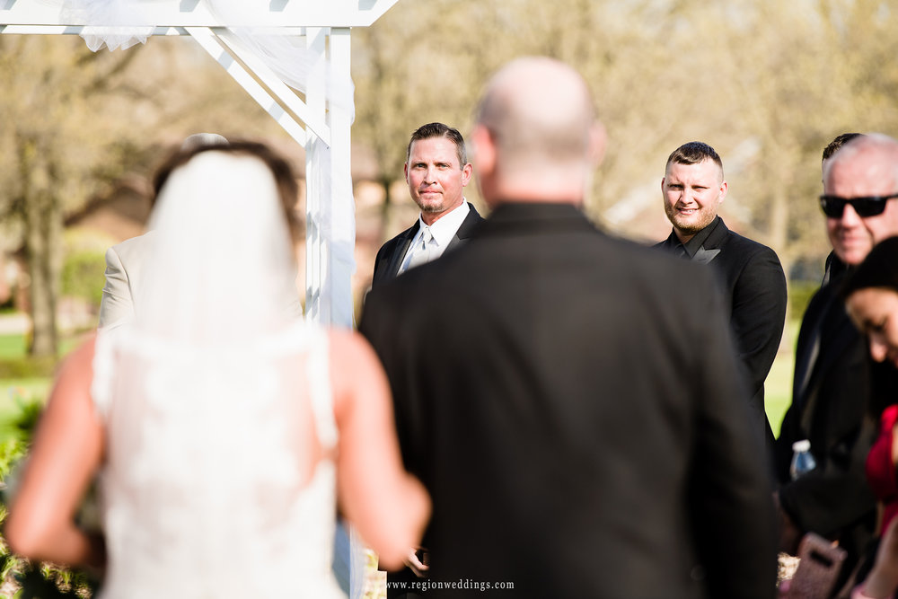 The groom watches his bride walk down the aisle with her Father by her side.