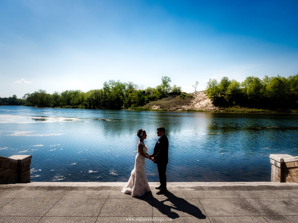 Bride and groom in silhouette at the Marquette Park Pavilion lagoon.