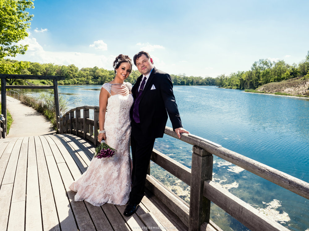 Bride and groom on the bridge overlooking the lagoon at Marquette Park Pavilion.