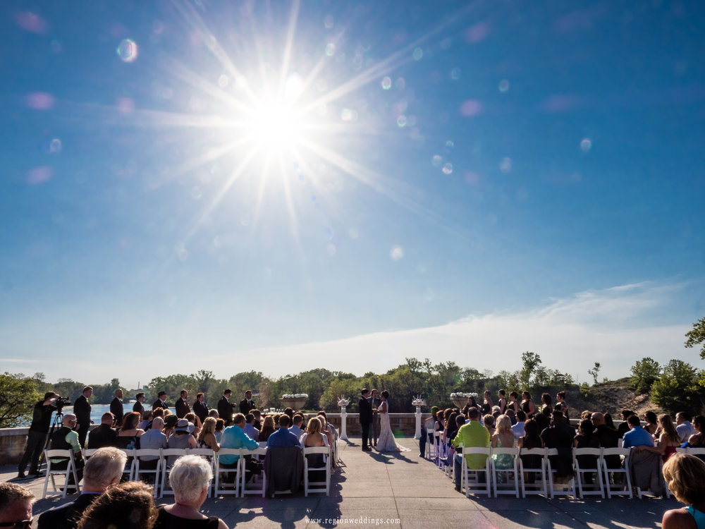 A sunstar illuminates an outdoor wedding.