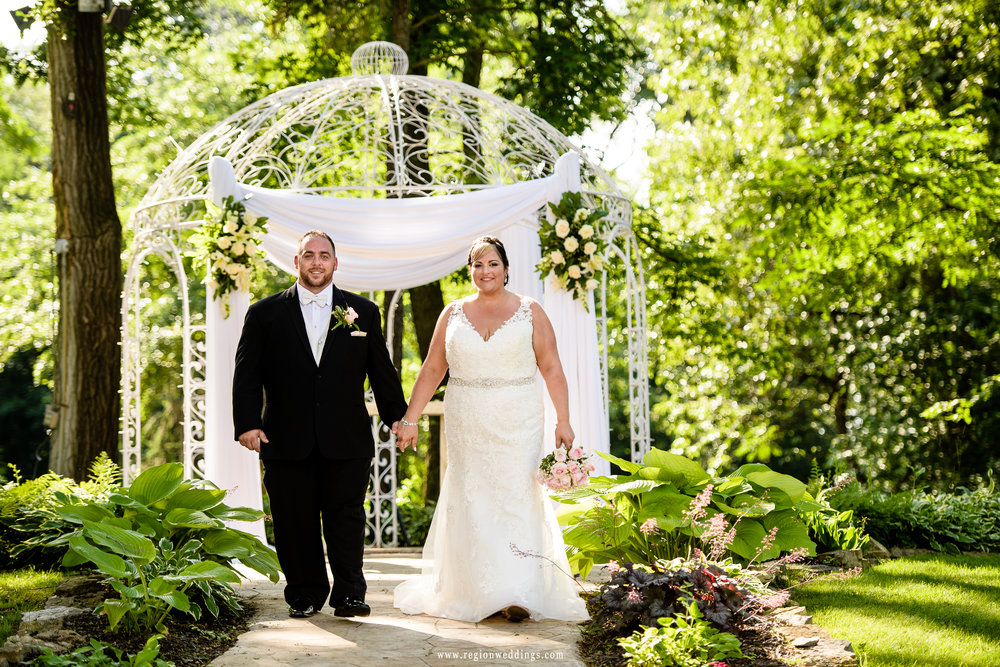 The groom walks his bride down the path from the gazebo.