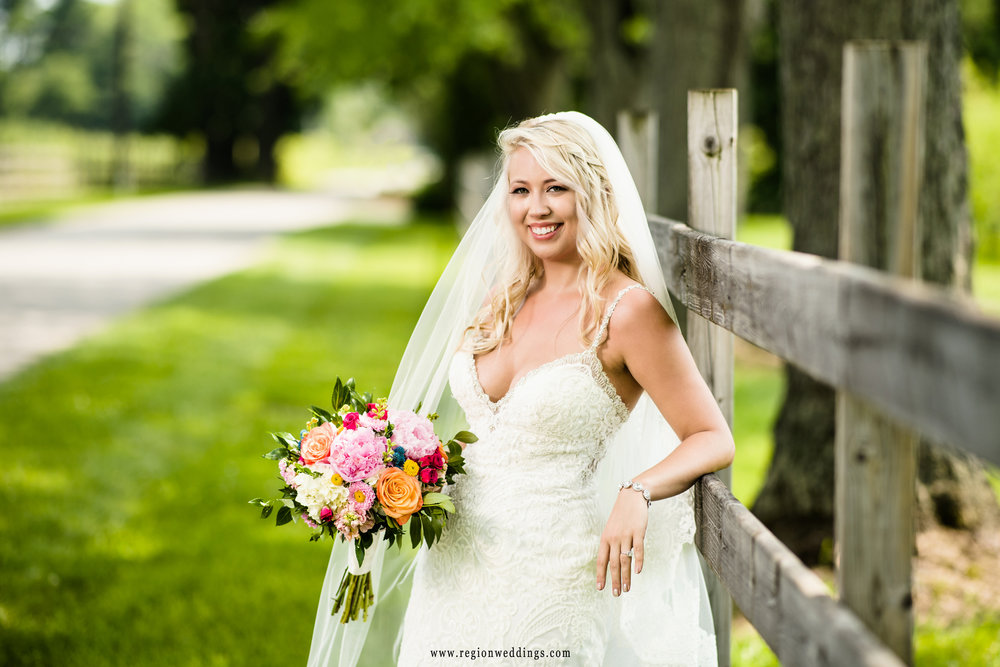 The bride leans back against the wooden fences of County Line Orchard.