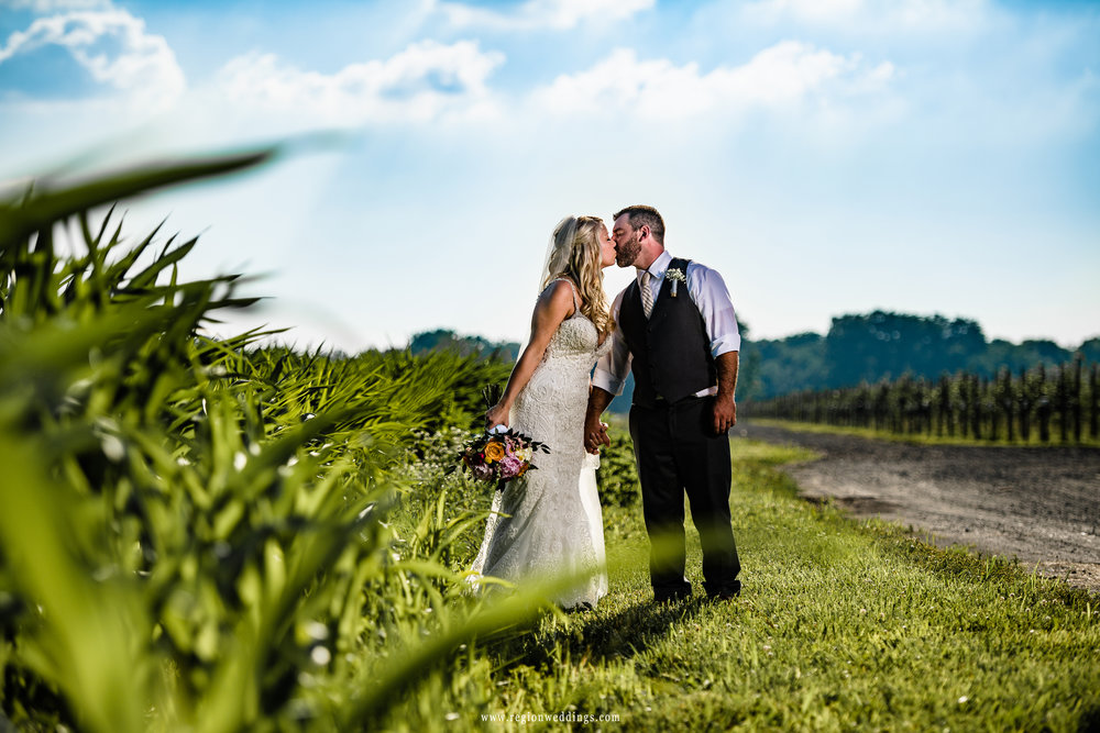 Bride and groom share a romantic kiss in the farm fields underneath a blue sky.