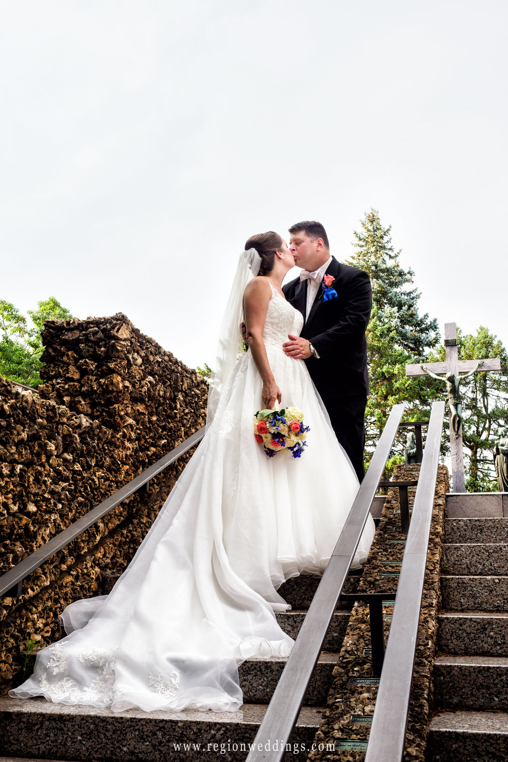 The bride and groom kiss on an outdoor staircase at Carmelite Shrine in Munster, Indiana.