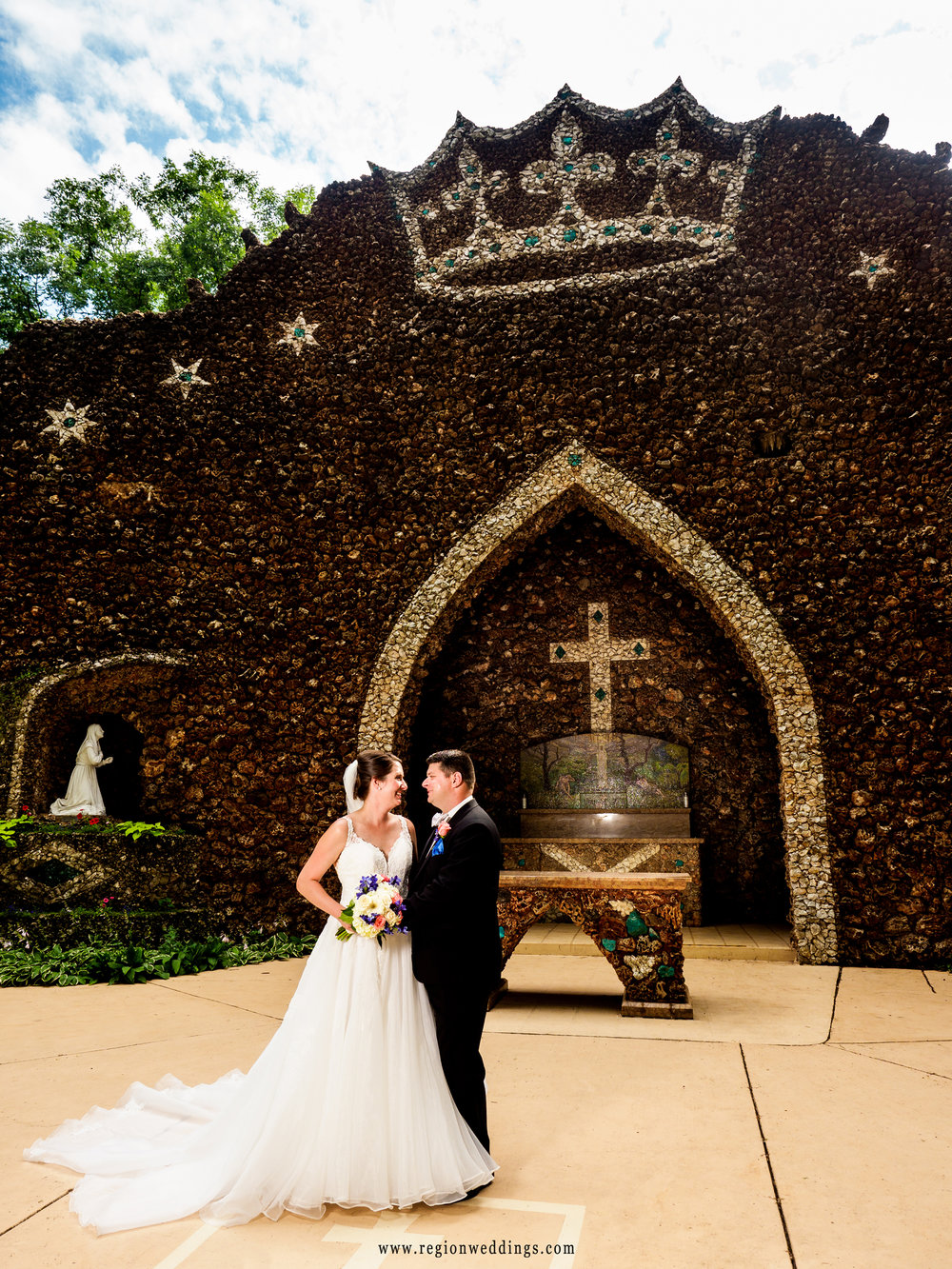 Bride and groom in front of the grotto at Carmelite Shrine.
