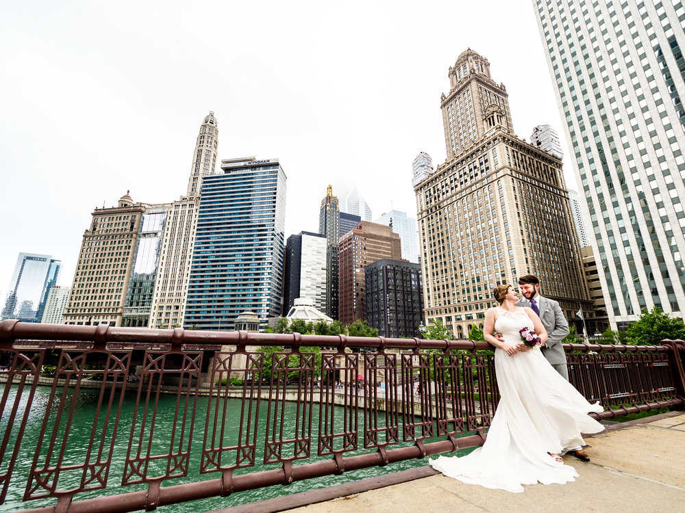 Bride and groom on the State Street bridge at the Chicago River with skyscrapers as a backdrop.