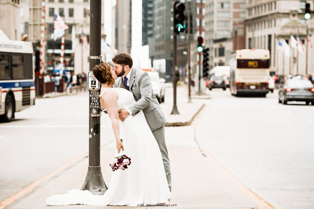 The groom dips his bride on Michigan Avenue as traffic passes by.