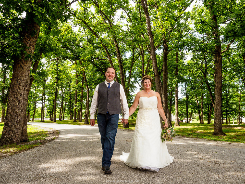 Bride and groom take a stroll underneath the tall oak trees of the fairgrounds in Crown Point.
