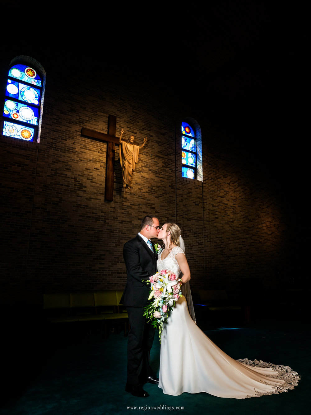 Stained glass windows overlook the bride and groom for their church wedding photos.