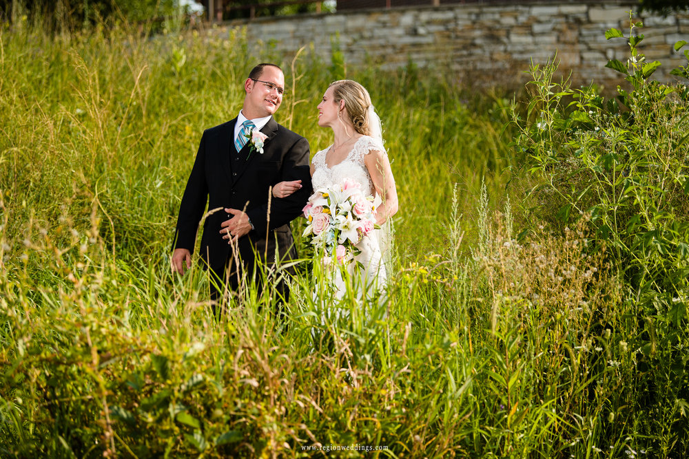 Bride and groom walk along the greenery at Centennial Park.