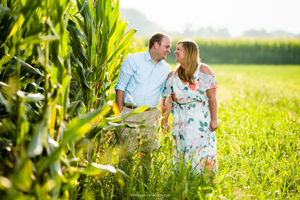 A fun couple shares a laugh walking along Indiana cornstalks.