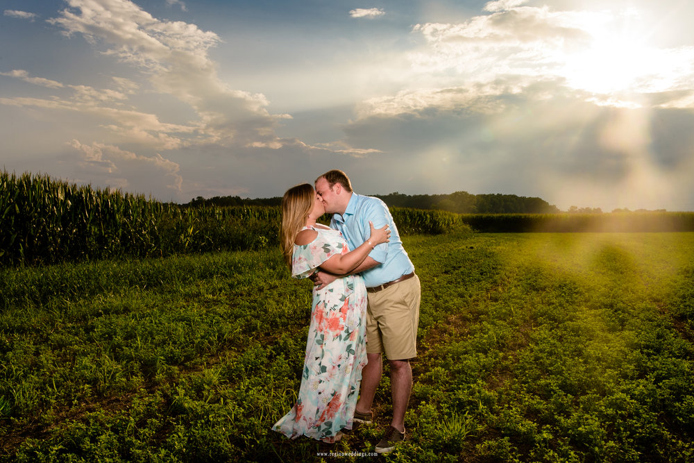 Sun rays come down from the sky onto a couple having a romantic moment in a field.